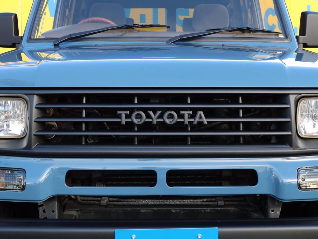 フロントグリルはマッドブラックに塗装し、とてもキレイな仕上がり★TOYOTA英字ロゴが良いですね★ | トヨタ ランドクルーザープラド 3.0 SXワイド ディーゼルターボ 4WD NEWアルルブルー クラシックコンプ