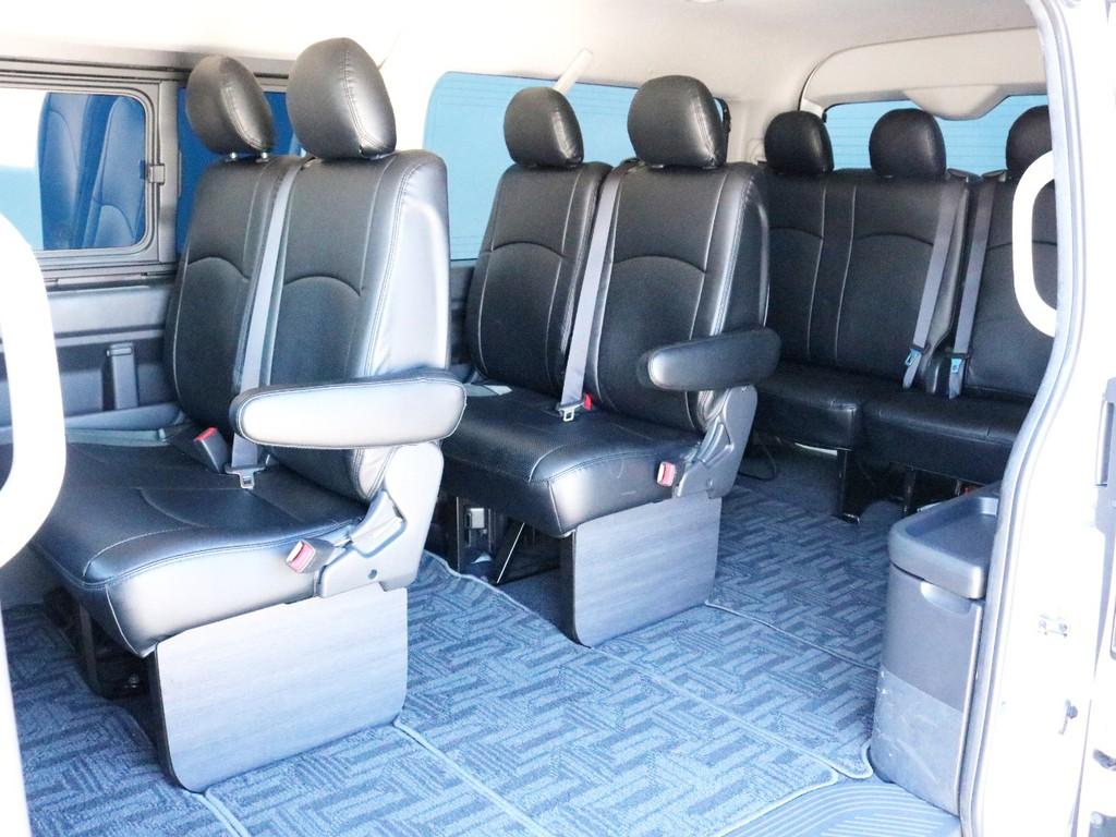 全席にレザー調シートカバーを装着済み! 足元にはむき出しのパイプフレームを隠すインテリアフッドパネルを装着済です。2列目、3列目シート左席にはひじ掛けが設置されています。